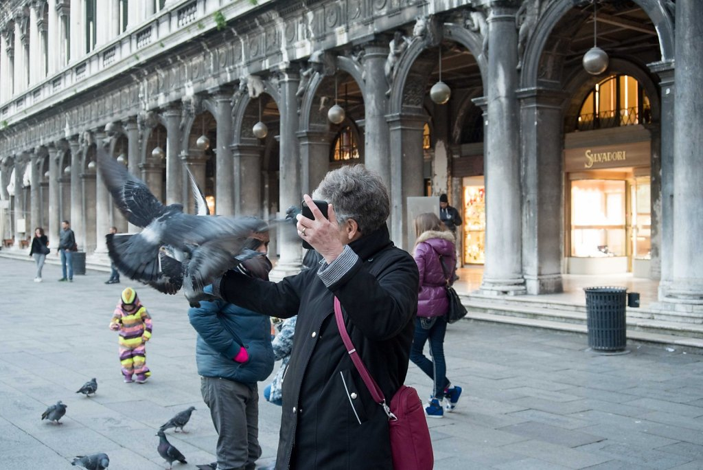 Woman trying to take a Selfie While feeding Pigeons